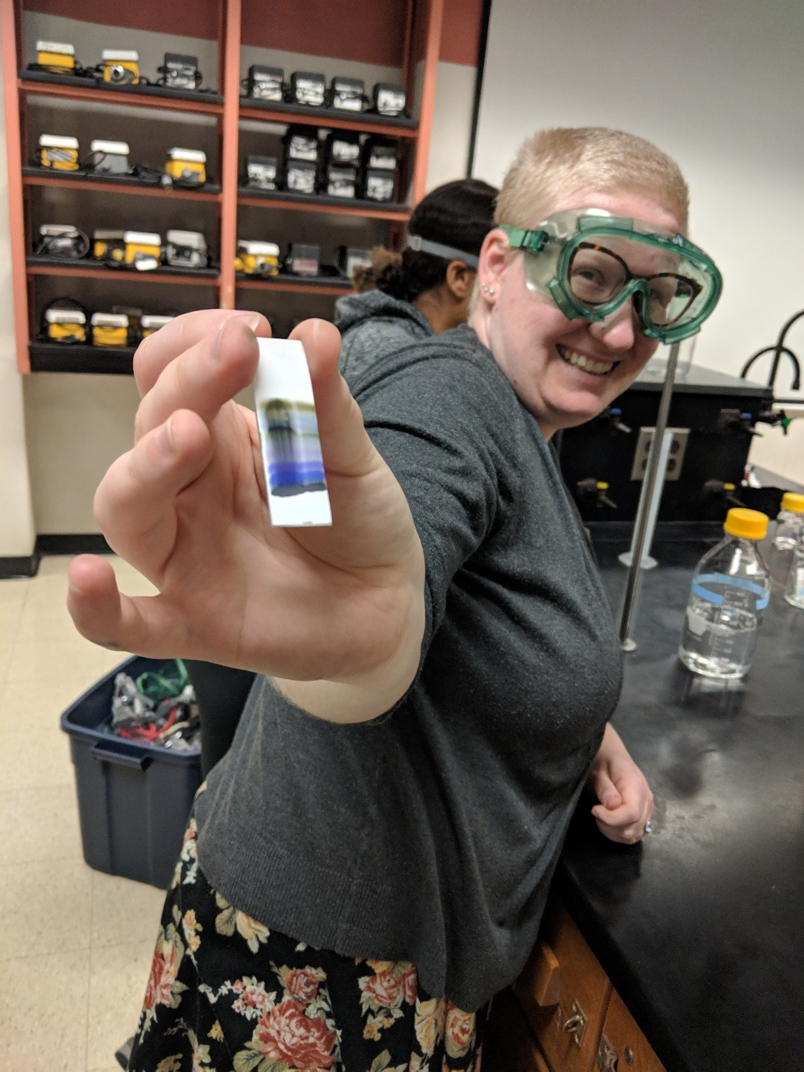A smiling volunteer holds up a strip of paper with blue and black separating dyes