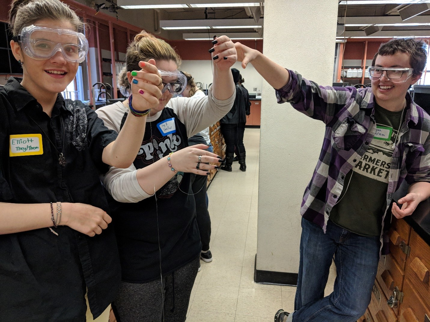 Students hold up strings of polymer that looks like fishing line